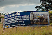 "Altamira, Para State, Brazil. Agrovila do km 18. FORT Xingu advertising hoarding which says ""Until When? Norte Energia: The families which will have their houses flooded by Belo Monte need and deserve to know where they are going to be taken to. That is their right."""