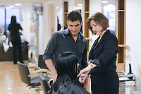 Instructor advises a student working on a client in the Arena Salon, Hair & Beauty Dept., Kingston College.