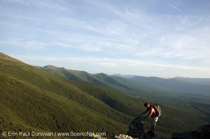 Hiker standing next to rock cairn along the Caps Ridge Trail in the White Mountains, New Hampshire USA.