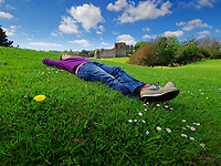 Pictured: A young woman enjoys the sunshine by Oystermouth Castle in Mumbles, near Swansea, Wales, UK. Saturday 12 June 2021<br /> Re: Hot and sunny weather enjoyed in most parts of the UK.