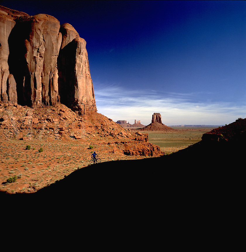 The distant silhouette of a mountain biker in the Monument Valley landscape. Arizona.