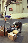 Third world poverty a man looks for food in rubbish bags for something to eat Buenos Aires Argentina South America. During economic crisis 2002 2000s