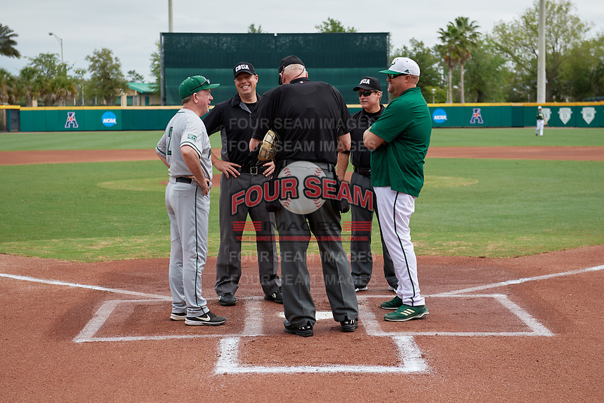 Dartmouth Big Green head coach Bob Whalen (2) during the lineup exchange with Billy Mohl and umpires Rick Darby, Luke Hamilton, and John Levin before a game against the USF Bulls on March 17, 2019 at USF Baseball Stadium in Tampa, Florida.  USF defeated Dartmouth 4-1.  (Mike Janes/Four Seam Images)