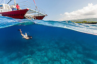 A woman snorkels in clear water off the Kona coast of the Big Island. (Note: The swimmer is model released, the man currently is not.)