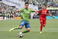 SEATTLE, WA - NOVEMBER 10: Kim Kee-hee #20 of the Seattle Sounders FC clears the ball away from Marky Delgado #8 of Toronto FC during a game between Toronto FC and Seattle Sounders FC at CenturyLink Field on November 10, 2019 in Seattle, Washington.