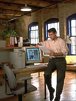 A young male professional leans against a computer and looks at documents in his modern loft office work space.