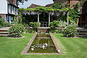 Wisteria-clad pergola and rectangular pool, Tidebrook Manor, East Sussex, early June.