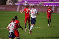 ORLANDO, FL - APRIL 24: Jacob Shaffelburg #24 of Toronto FC and Ranko Veselinovic #4 of Vancouver Whitecaps battle for the ball during a game between Vancouver Whitecaps and Toronto FC at Exploria Stadium on April 24, 2021 in Orlando, Florida.