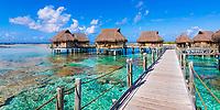 Luxury overwater bungalows and pier above turquoise Tikehau atoll lagoon and coral reefs, Tuamotus Archipelago, French Polynesia, South Pacific Ocean