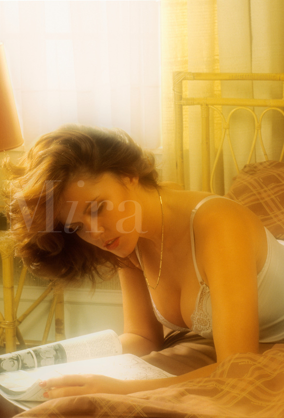 Young woman lying on her bed reading a magazine.