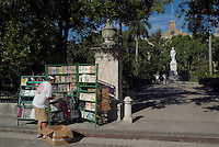 Man stocking his bookstall on Plaza de Armas square near a statue of Carlos Manuel de Cespedes, Havana, Cuba.