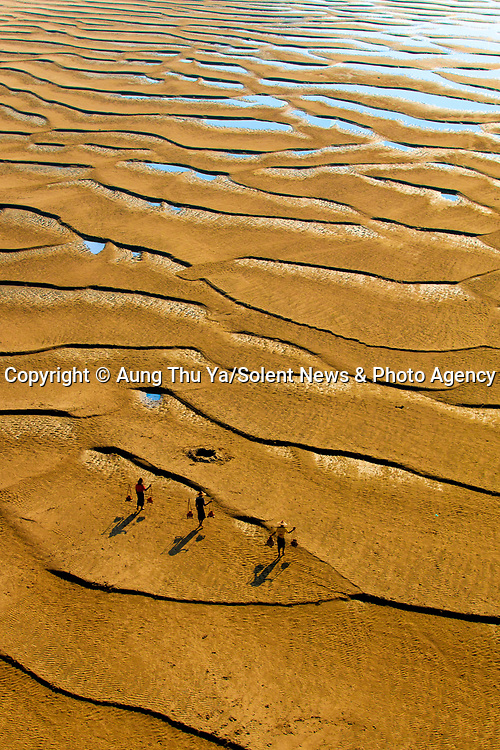 """Local villagers carrying water are dwarfed by the size of sprawling sandbanks in golden morning sunlight in Pakokku City, Myanmar.<br /> <br /> The images were captured by Aung Thu Ya, 37, a government officver from Myanmar in the dry intermonsoonal season season.  Myanmar, has three seasons in a year, the cool, relatively dry northeast monsoon (late October to mid-February), the hot, dry intermonsoonal season (mid-February to mid-May), and the rainy southwest monsoon (mid-May to late October).<br /> <br /> Aung said, """"The sandbanks lie alongside the Ayeyarwady River.  The waterway is a vital lifeline for Myanmar - it's the most commercial in the region, supplying fish to local people.""""<br /> <br /> """"In this dry season, villagers pass through the sandbanks when carrying water and accessing the boat terminal.  The golden light occurs between 8 and 10am in the morning."""" <br /> <br /> Please byline: Aung Thu Ya/Solent News<br /> <br /> © Aung Thu Ya/Solent News & Photo Agency<br /> UK +44 (0) 2380 458800"""