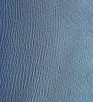 aerial photograph straight down onto the surface waves of the Pacific Ocean