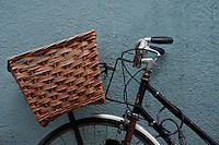 A classic bicycle with a woven basket leans against a blue wall in Oxford, though this style of bike is more popular in Cambridge.