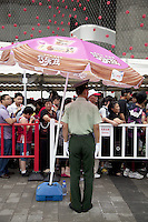 China. Shanghai. World Expo. Expo 2010 Shanghai China.  A policeman stands in front of a line of chinese tourists waiting to enter the Switzerland Pavilion. Pink ice cream sunshade with drawings and chinese writings used for advertisements. White glove and cap. The interactive, intelligent facade enveloping the swiss pavilion is a curtain of woven aluminium elements under which visitors pass to access the urban area on the ground floor of the building. LED lights comprised of an energy source, a storage unit and a consuming unit are incorporated into the facade. The energy produced is made visible in the form of flashes that are triggered by the pavilion surroundings, such as the sun or flashes made by visitor cameras. Thanks to the storage of energy in each individual cell, the facade is also active at night, when the cells will trigger each other.27.06.10  © 2010 Didier Ruef