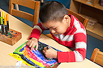 Education prechool art activity boy drawing with markers using left hand