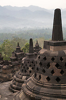 Borobudur, Java, Indonesia.  Temple Stupas in Early Morning Mist.  The diamond-shaped holes symbolize the passions that still linger as men rise toward Nirvana.  On the next higher terrace the holes in the stupas are square, symbolizing  the overcoming of passions as one approaches Nirvana.