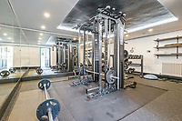 BNPS.co.uk (01202 558833)<br /> Pic: Savills/BNPS<br /> <br /> Pictured: The gym.<br /> <br /> A striking turreted French style chateau in one of the UK's most desirable streets is on the market for £9.25m.<br /> <br /> Deauville is an impressive mansion with a striking period exterior but a stylish contemporary look inside and all the mod cons a home owner would want, including an indoor pool complex and cinema room.<br /> <br /> The house is in the prestigious St George's Hill estate in Weybridge, Surrey, which is renowned all over the world.<br /> <br /> The five-bedroom house was built in 2000 but has undergone an extensive refurbishment in the last few years.