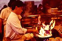 Chef Roy Yamaguchi with flaming pan at his restaurant in Hawaii Kai, Oahu