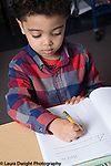 Education Preschool Childcare 3-4 year olds boy starting day by signing into his notebook