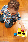 12 month old baby boy kneeling on floor playing with shape sorter, trying different spots for ball
