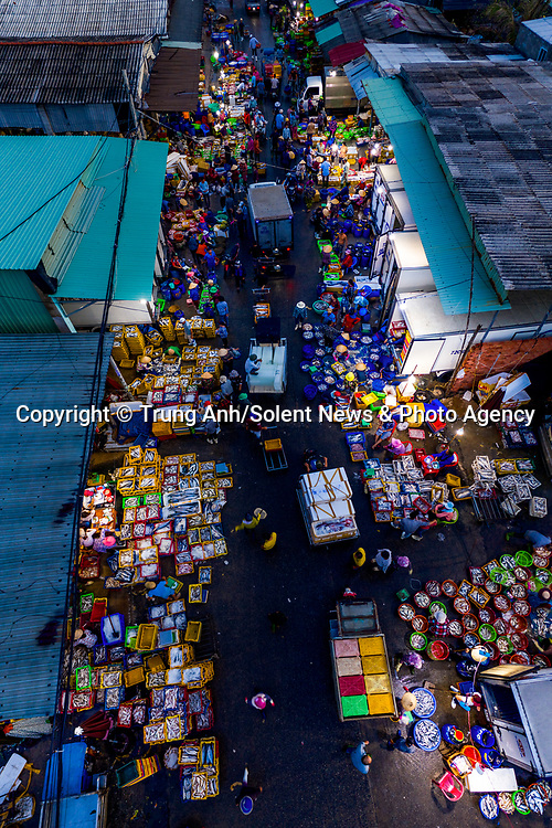 Hundreds of fish traders sell newly caught fish in bright colourful boxes to buyers at night in the  Long Hai fish market in Vietnam. <br /> <br /> Thousands of customers flock from across Vietnam to buy fish being sold at the market, which runs from midnight to around 6am. <br /> <br /> The spectacular shots were captured by photography Trung Anh. <br /> <br /> The daily market is the largest in the Vung Tau Province of Vietnam and sell wholesale fish to shop owners across the region. <br /> <br /> Please byline: Trung Anh/Solent News<br /> <br /> © Trung Anh/Solent News & Photo Agency<br /> UK +44 (0) 2380 458800