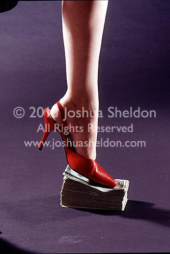 Woman's high heel shoe standing on stack of dollar bills<br />
