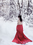 Beautiful half nude woman with bare back in red kimono lowered down to her waist walking away into a snowy winter scenery Image © MaximImages, License at https://www.maximimages.com