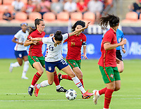 HOUSTON, TX - JUNE 10: Joana Marchao #5 and Dolores Silva #14 of Portugal battle Christen Press #23 of the United States for control of the ball during a game between Portugal and USWNT at BBVA Stadium on June 10, 2021 in Houston, Texas.