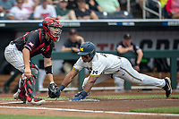 Michigan Wolverines designated hitter Jordan Nwogu (42) slides safely home as Texas Tech Red catcher Braxton Fulford (26) waits for the throw during the first inning of the NCAA College World Series on June 15, 2019 at TD Ameritrade Park in Omaha, Nebraska. Michigan defeated Texas Tech 5-3. (Andrew Woolley/Four Seam Images)