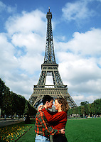 A romantic couple poses in an embrace in front of the Eiffel Tower. Paris, France.
