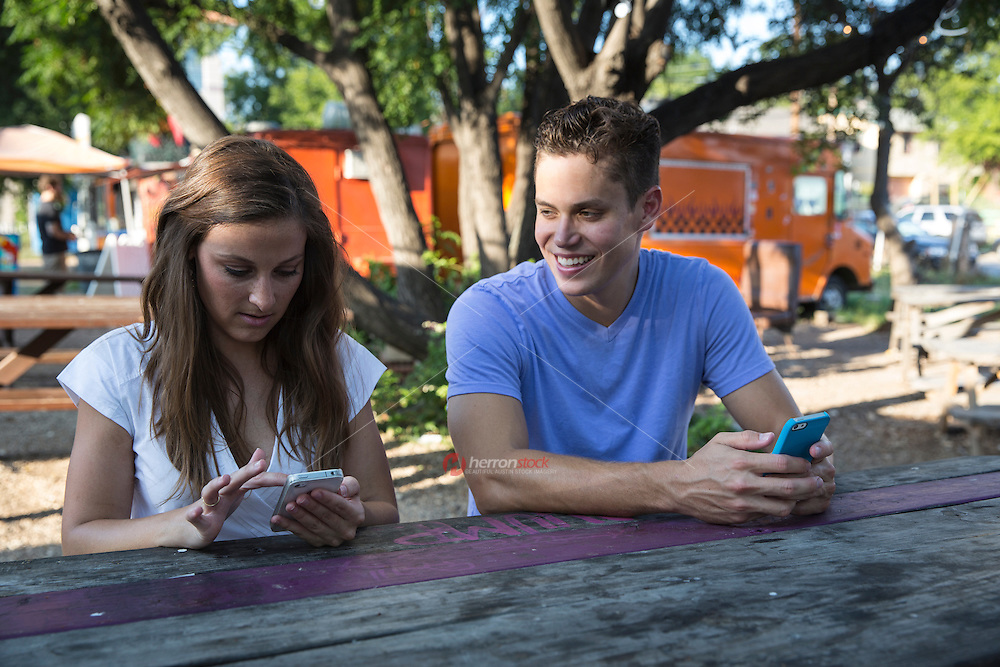 Young couple planing pub crawl on mobile smart phones in East 6th Street, Eastside, East Austin.