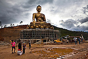 Children and young people seen around a Buddha Dordenma - a gigantic Shakyamuni Buddha statue under construction overlooking the southern approach to Thimphu, Bhutan. Upon completion, it will be one of the largest Buddha in the world, at a height of 169 feet (51.5 meters). Photo: Sanjit Das/Panos