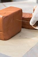 Wildbienen-Nisthilfe aus Ton. Ein Tonblock wird mit einem Draht in kleinere Stücke zerschnitten. Besteht aus Tonblöcken mit unterschiedlichen dicken, breiten Löchern, Wildbienen-Nisthilfen, Wildbienen-Nisthilfe selbermachen, selber machen, Wildbienenhotel, Insektenhotel, Wildbienen-Hotel, Insekten-Hotel