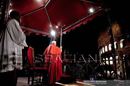 Pope Benedict XVI prays as a faithful holds the cross during the traditional Via Crucis (Way of the Cross) at the Colosseum in Rome April 6, 2007.