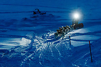 With his headlamp shining the way, Linwood Fiedler runs on the Yukon River as he approaches the Kaltag checkpoint on Sunday  morning March 10th during the 2019 Iditarod Trail Sled Dog Race.<br /> <br /> Photo by Jeff Schultz/  (C) 2019  ALL RIGHTS RESERVED