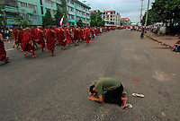 A man prays to show solidarity with protesting Buddhist monks calling for the overthrow of the country's military junta. The public's anxiety about the safety of the protesters is palpable. Thousands took to the streets again despite a new threat that the military would shoot on sight any gatherings of over four people.
