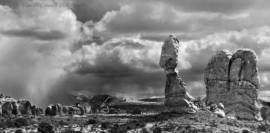 An early springtime storm brings rain and snow down from the La Sal Mountains towards the iconic Balanced Rock in Arches National Park.  The last remaining sunlight illuminates the profile of the formation as well as some of the precipitation falling from the sky.  Far in the distance Turret Arch can be spotted over this grand landscape.<br /> <br /> Tech. info. – Toyo 45A, 210mm, Red filter, FP4, ¼ s @f45, dev. HC110, wet-mount scan Epson V750, cropped and finished in PS