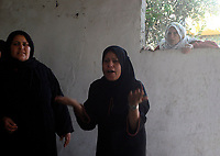 """Relative of Maateg family during the funeral of four children and their mother from the Abu Maateq family in Beit Hanun, in the Gaza Strip on April 28, 2008. Four children, aged one to five, their mother and a militant were killed in Israeli operations in Gaza today as Palestinian factions headed to Egypt for talks on a possible truce. The four siblings -- aged one, three, four and five -- were killed when a tank shell hit their home in the town of Beit Hanun, and their mother died later of her wounds, doctors at the Kamal Radwan hospital said..""""photo by Fady Adwan"""""""