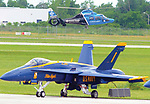 A CareFlight helicopter flies past one of the Blue Angels FA-18 aircraft as the Vectren Dayton Air Show celebrates the 35th anniversary of CareFlight service to the Miami Valley with a special three-ship fly-by.