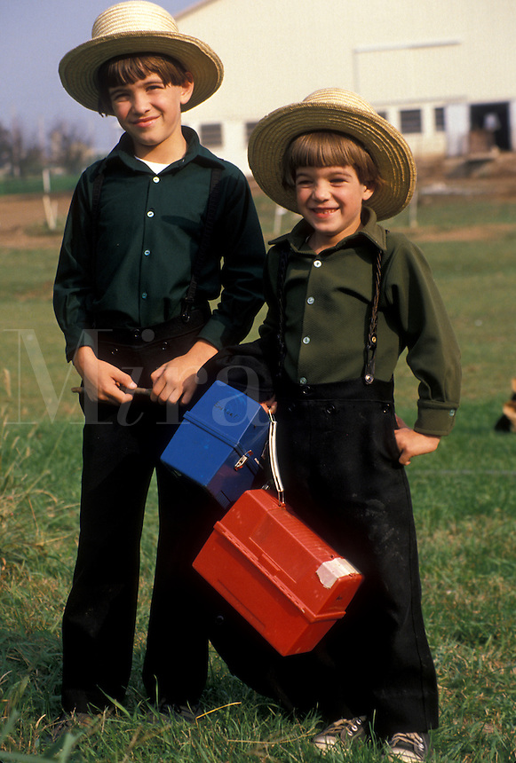 "AJ2219, Amish, children, Pennsylvania, Lancaster County, White Horse, Two Amish boys in front a farm waiting for the """"Buggy Bus"""" going to school in Lancaster County. The boys are wearing green shirts with black pants and traditional straw hats. They are carrying lunch boxes."