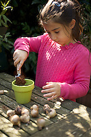 Young girl (seven year old) putting soil into pot