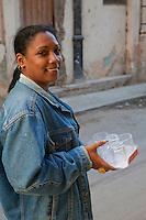 Cuba, Havana.  Afro-Cuban Woman Carrying Six New Glasses Home.