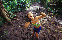 Girl in the mud playing while hiking Maunawili Trail, Kailua, Oahu, Hawaii