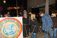 """A number of Occupy Orange County protestors hold the """"Occupy Orange County in unity with Occupy Wall Street"""" while marching at South Coast Plaza early in the morning (12:55am).  The Macy's Men's Store is visible in the background.  The protesters were tied together by rope, being led by a single protestor dressed in a suit (as a banker), symbolizing how the 1% lead the 99%."""