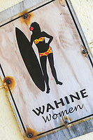 "A weathered ""Wahine Women"" restroom sign at Honoli'i Beach Park, Big Island."