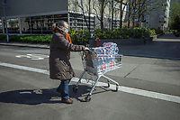 """Switzerland. Canton Ticino. Lugano. An elderly woman wears a mask on the face to protect herself from the Coronavirus (also called Covid-19). She pushes a supermarket trolley fully loaded with plastic bottles of water. She bought them in order to stock water bottles at home. Swiss Alpina mineral water rises up through the Valais Alps. Deep inside the mountains, the water is naturally purified and enriched with minerals, which gives this absolutely natural product its unique flavour. Swiss Alpina is a mineral water from the heart of the Swiss Alps.. Due to the spread of the coronavirus, the Federal Council has categorised the situation in the country as """"extraordinary"""". It has issued a recommendation to all citizens to stay at home, especially the sick and the elderly. The Federal Council (German: Bundesrat, French: Conseil fédéral, Italian: Consiglio federale, Romansh: Cussegl federal) is the seven-member executive council that constitutes the federal government of the Swiss Confederation. Coop is one of Switzerland's largest retail and wholesale companies. It is structured in the form of a cooperative society with around 2.5 million members. 24.03.2020 © 2020 Didier Ruef"""