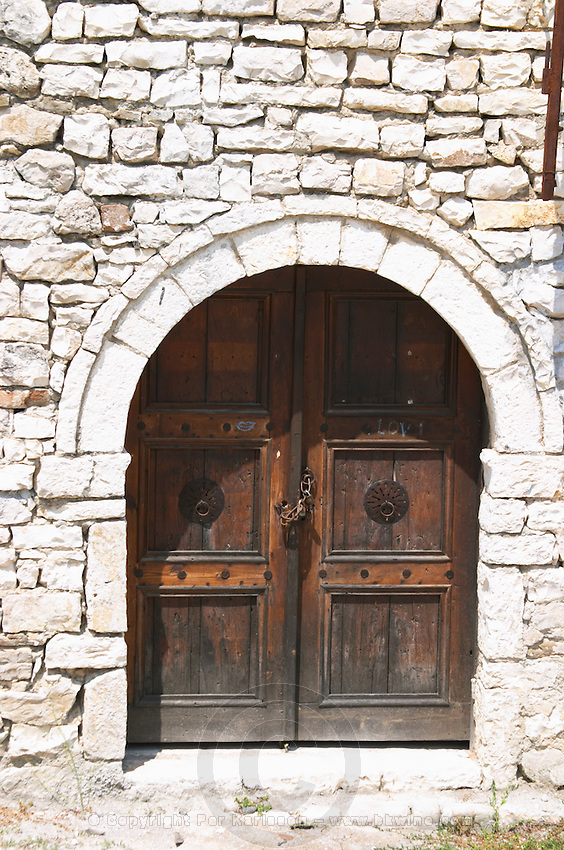 Stone wall with old wooden door with chain and pad lock. Berat upper citadel old walled city. Albania, Balkan, Europe.