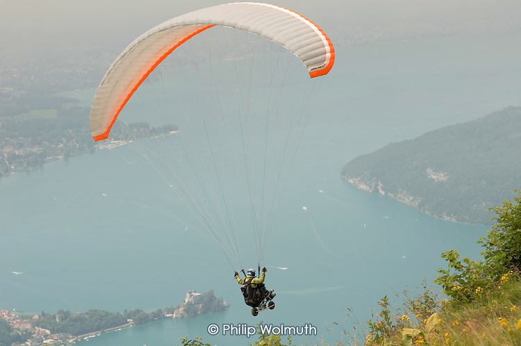 A wheelchair user hang-glides over Lake Annecy in the French Alps, having used a two-wheeled scooter to launch himself from the mountainside.