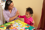 """Two year old toddler girl with mother playing with peg puzzle mother giving her """"high 5"""" congratulations when she finishes"""